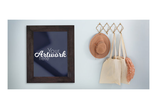 Picture Frame Mockup on Blue Wall with Hanging Hat and Bags