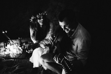 Atmospheric black and white photo on which the happy spouses spend time together sitting by the bonfire on the beach. Man playing the guitar