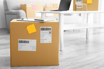 Parcel ready for shipment to customer on floor in home office. Startup business