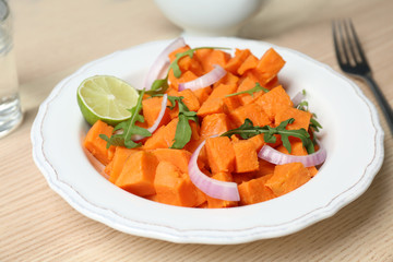 Plate with delicious cut sweet potato on table