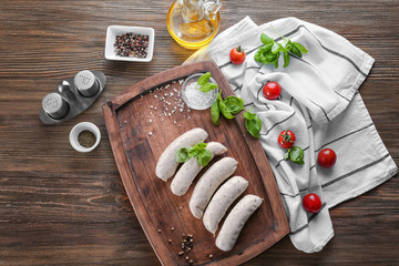 Delicious white sausages on wooden board