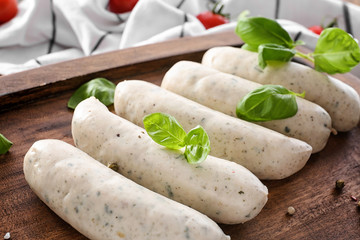Delicious white sausages on wooden board, closeup