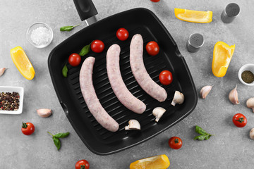 Flat lay composition with grill pan, sausages and vegetables on grey background
