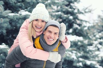 Happy loving couple having fun in winter park