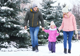 Happy family walking in winter park