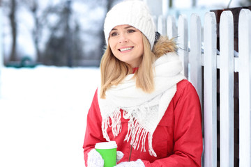 Attractive woman drinking coffee outdoors on winter day