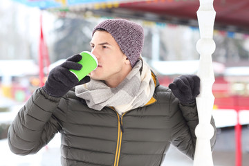 Handsome man drinking coffee outdoors on winter day