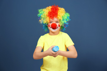 Cute little boy with clown makeup and party popper on color background. April fool's day celebration