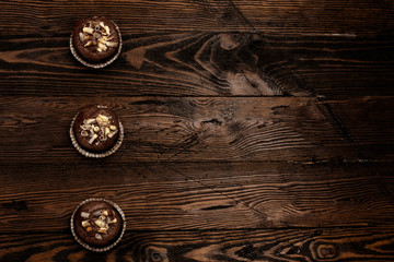 chocolate cupcakes on a brown wooden background decorated with chocolate shaving