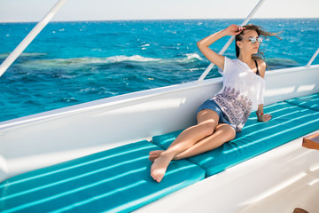 Young beauty woman lying on a private yacht in the sea