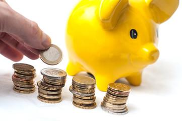 tirrelire jaune en forme de cochon et euros en billets et pièces de monnaie empilées