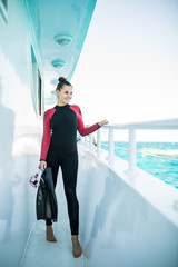 Young diver girl in black wetsuit standing on board of the yacht