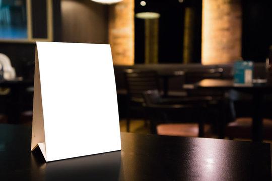 Mockup white label menu frame on table with cafe restaurant interior background