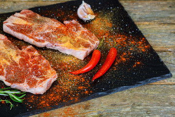 meat pork steak on the wood background with ingredients herbs and spices.