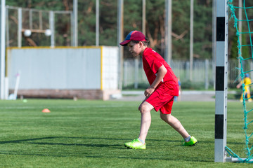 kid is going to catch a ball on the football training at the stadium