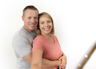 young beautiful happy and attractive romantic couple with husband and wife or girlfriend and boyfriend taking selfie self portrait photo with stick