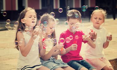 Four kids blowing soap bubbles