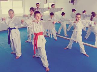 Children training karate kicks during karate class