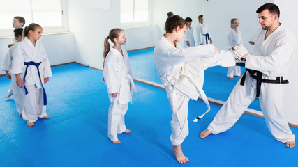 Boys kicking with coach during karate class