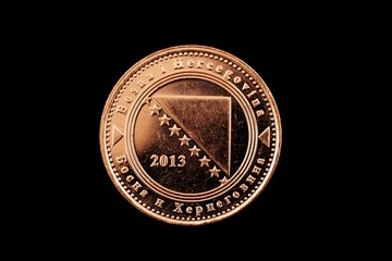 A macro image of a Bosnian 50 fenings coin isolated on a black background