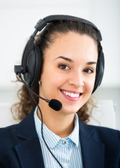 girl with headset and laptop in office.