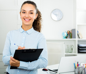 Business lady with pad standing near office desk