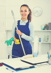 Adult woman in uniform cleaning in office