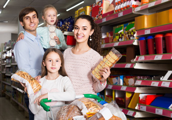 parents with two kids choosing biscuits in store