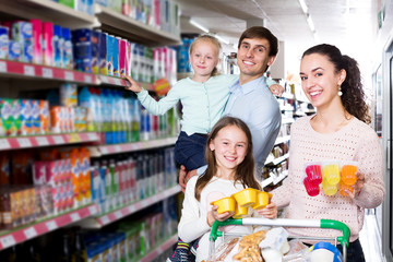 Parents with two kids buying fruit yoghurt