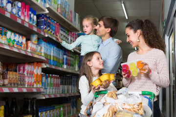 Family purchasing yoghurts in supermarket.