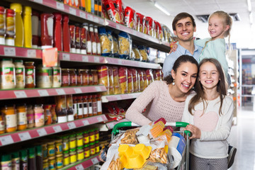 parents with two kids and purchases in shopping cart