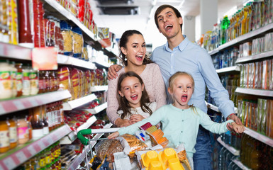 Happy customers with children buying food in hypermarket