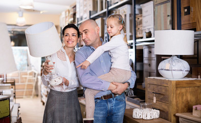Happy family is choosing new lamp for home in the furniture store.