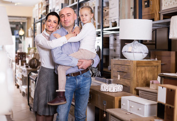 Family couple with small daughter in furniture shop