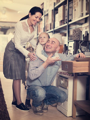 couple with the daughter choosing furniture