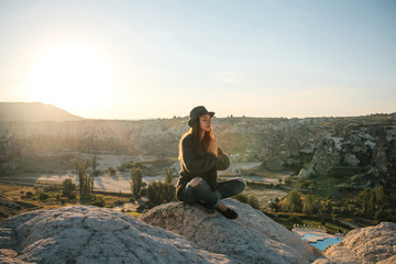 Young beautiful girl practicing yoga at the top of a mountain in Cappadocia at sunrise. Practices of relaxation.