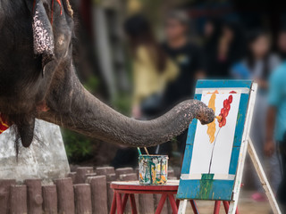 Artist elephant is painting picture of colorful flowers at Samutprakarn crocodile farm and zoo Thailand