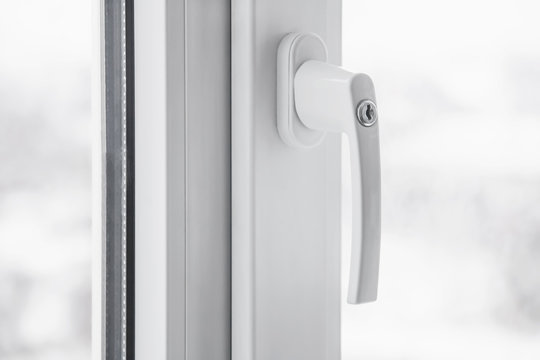 White secure UPVC window with lockable handle. Closeup, selective focus