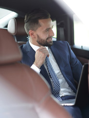 Close-up of a successful businessman sitting in a comfortable car