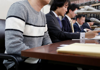 A man in his 20s who had invested 400,000 yen in digital money at Coincheck, attends a news conference with lawyers after a group of seven investors filed a suit at the Tokyo District Court, in Tokyo