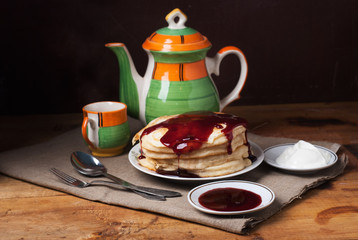 Still life of pancakes to pour the berry syrup,
