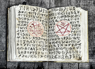 Open black magic book with evil symbols and pentagram on shabby pages. Halloween, occult, esoteric and wicca concept. Vintage background