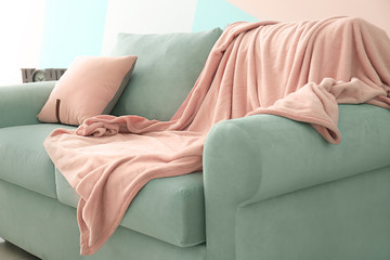 Comfortable mint couch with cushion and blanket in living room