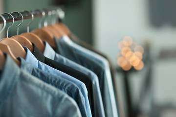 Clothes rack with many shirts indoors, closeup. Fashionable wardrobe Wall mural