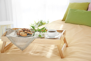 Tray with tasty breakfast and flowers on bed