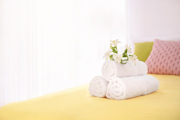 Rolled white towels with flowers on bed
