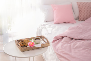 Tray with tasty breakfast and tulip on table near bed
