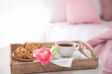 Tray with tasty breakfast and tulip on bed