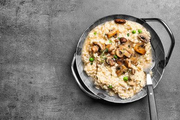 Dish with delicious risotto and mushrooms on grey background