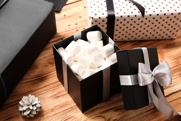 Beautiful gift box with sweets on table